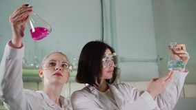 Chemical laboratory. Two young lab technicians making experiments with liquids. Evaluate the result of their experiment stock footage