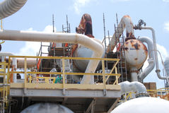 Chemical Plant Detail. A detail of a process unit in a chemical plant, with exchangers, piping and valves against a blue sky Stock Images