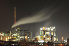 Chemical plant by night. Pharmaceutical industry by night with furnace in background and steam clouds over it Royalty Free Stock Photos
