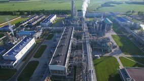 Chemical Plant produces gasoline and mineral fertilisers. Aerial flying centrally morning sunshine summer fields and