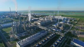 Chemical Plant produces gasoline and mineral fertilisers. Aerial flying morning sunshine summer fields and grass around