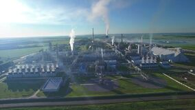 Chemical Plant produces gasoline and mineral fertilisers. Aerial orbit circle flying morning sunshine summer fields and