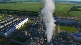 Chemical Plant produces gasoline and mineral fertilisers. Long orbit round aerial flying morning sunshine summer fields
