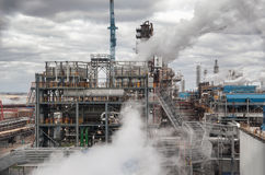 Chemical plant for production of ammonia and nitrogen fertilization on day time. The steam from the cooling system Stock Photos