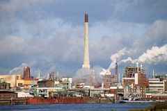 Chemical plant at a river by day. Big Chemical plant on riverside with smoking chimneys stock image