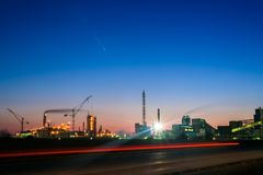 Chemical plant in a silhouette image at sunset, the glowing light of the chemical industry at sunset and twilight sky, the field stock photo