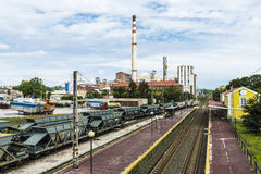 Chemical plant of Solvay company, Spain. Torrelavega, Spain - August 9, 2016: Chemical plant of Solvay company with cargo trucks parked and wagons stopped in Royalty Free Stock Image