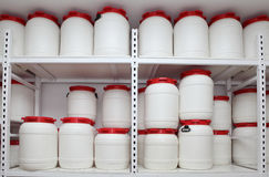 Chemical plastic barrels on shelves in storehouse Royalty Free Stock Photos
