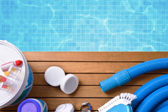 Chemical products and tools for pool maintenance. Chemical products and tools for the maintenance of the pool on wooden slats. Pool with water and blue mosaics Stock Photo