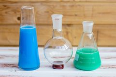 Chemical reagents in glass flasks. Green and blue stock photo