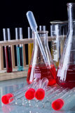 Chemical recipients on glass table. Against dark background - closeup Royalty Free Stock Images