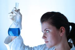 Chemical research 04. Young female scientist on blue background Royalty Free Stock Photos