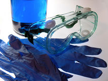 Chemical Safety. Blue reagent with safety goggles and gloves Royalty Free Stock Photo