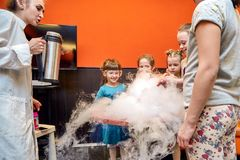 Chemical show for kids. Professor carried out chemical experiments with liquid nitrogen on Birthday little girl. royalty free stock image
