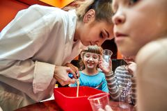 Chemical show for kids. Professor carried out chemical experiments with liquid nitrogen on Birthday little girl. royalty free stock images
