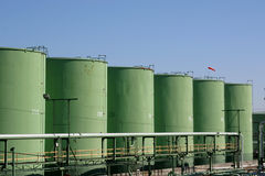 Chemical Storage Tanks. Green chemical storage tanks in a row against a clear blue sky Royalty Free Stock Photography