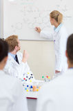Chemical student write chemical formula on the blackboard Royalty Free Stock Images