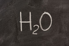 Chemical symbol of water on blackboard Stock Photo