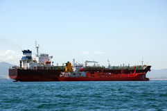 Chemical tanker being refuelled. A chemical tanker which is anchored being refuelled by a fuel barge at sea Royalty Free Stock Images