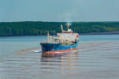 Chemical Tanker vessel sails upstream the Song Long River. Chemical Tanker vessel sails upstream the Song Long River from Vung Tau bay to Ho Chi Minh City stock photo