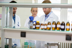 Chemical technicians perform experiment in lab. Group of young chemical technicians perform experiment in lab Royalty Free Stock Image