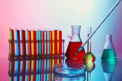 Chemical test-tubes with medicine dropper. On color background stock images