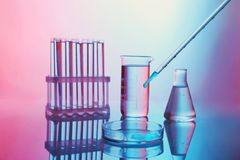 Chemical test-tubes with medicine dropper. On color background royalty free stock images
