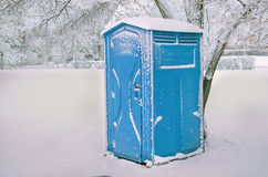 Chemical toilet in the park on winter. Blue outdoor chemical toilet in the park on winter stock photos