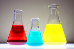 Chemicals. Red, blue and yellow liquid chemicals in flasks Stock Photos