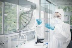 Chemicus in beschermend kostuum die met futuristisch interfaceverstand werken stock fotografie