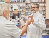 Chemicus die geneesmiddelen aanbieden aan oude klant in apotheek royalty-vrije stock afbeeldingen