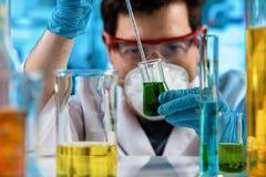 Chemicus die steekproef van vloeistoffen in het onderzoeklaboratorium meten stock afbeelding