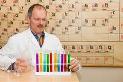 Chemicus het vullen glazen buizen met gekleurde vloeistoffen Stock Fotografie