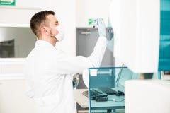 Chemicus lopende bloedonderzoeken in een laboratorium Stock Afbeeldingen