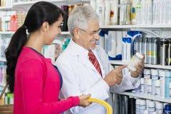 Chemicus Pointing At Product terwijl Status door Vrouwelijke Klant stock foto's