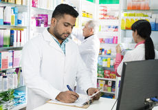 Chemicus Writing On Clipboard terwijl Collega's die in Pharmac werken royalty-vrije stock afbeeldingen