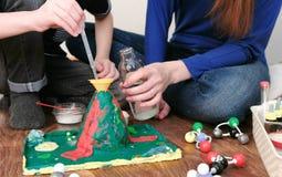 Chemiczny eksperyment Zakończenie chłopiec ` s wręcza polaną wodę od butelki w leja wulkan używać a fotografia stock
