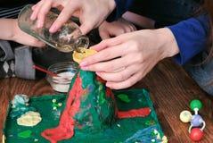 Chemiczny eksperyment Zakończenie kobiety ` s wręcza polaną wodę od butelki w leja wulkan obrazy royalty free