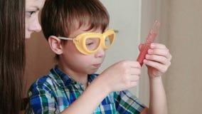 Chemie experimentiert zu Hause Junge erklärt seiner Mutter die chemische Reaktion und hält ein Reagenzglas in seiner Hand stock video