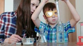 Chemie experimentiert zu Hause Junge gießt Wasser von der Flasche in die Flasche unter Verwendung einer großen Pipette stock video