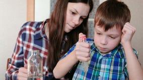 Chemie experimentiert zu Hause Junge rüttelt das Reagenzglas, um die Substanzen in ihm zu mischen stock video