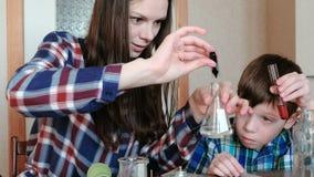 Chemie experimentiert zu Hause Mutter gießt Wasser von der Flasche in die Flasche unter Verwendung einer großen Pipette stock footage