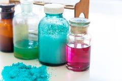 Chemieflessen die diverse substanties van verschillende kleuren bevatten die zich op die laboratoriumlijst bevinden over een stap Stock Foto