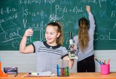 Chemieklassen De meisjesklasgenoten bestuderen chemie De chemische reacties van microscoopreageerbuizen Leerlingen bij bord stock afbeeldingen
