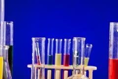 Chemielaboratorium met gekleurde terug vloeistoffen op een lijst over blauw wordt geplaatst dat Royalty-vrije Stock Fotografie
