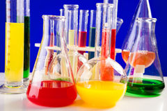 Chemielaboratorium met gekleurde terug vloeistoffen op een lijst over blauw wordt geplaatst dat Stock Fotografie