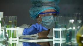 Chemiestudent die reactie in reageerbuizen controleren, die gegevens toevoegen om over lusje te rapporteren stock videobeelden