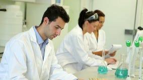 Chemiestudenten die aan een experiment samenwerken stock video