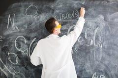 Chemik pisze chemicznej formule na blackboard obraz royalty free