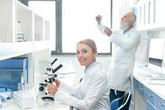 Chemik pracuje z mikroskopem podczas gdy jej kolega patrzeje kolbę behind w chemicznym laboratorium Obraz Stock